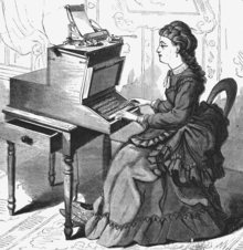A woman in a long, frilled dress with a pleated train sits at a large, wooden typewriter which is approximately half her size. The typewriter is affixed to a small table with an open drawer.