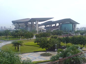 A far view of a stadium, with two large sitting pavilions and greenery around the compound.