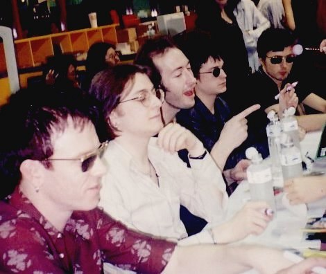 Five men sitting at a table at a press conference