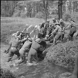 Queen's Own Worcestershire Hussars - Men of 53rd Anti-Tank Regiment, Royal Artillery, manhandle a 2 Pounder Anti-Tank gun across a stream near Thirsk in Yorkshire, 26 May 1942. (IWM H20128)