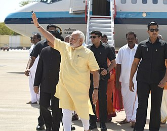 Special Protection Group - PM Modi followed by SPG personnel wearing safari suits and sunglasses.