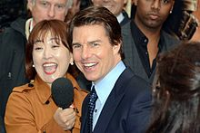 Tom Cruise being interviewed at a film premiere.