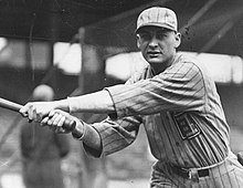 A man in a light-colored pinstriped baseball uniform looks into the camera having just swung his bat to the left.