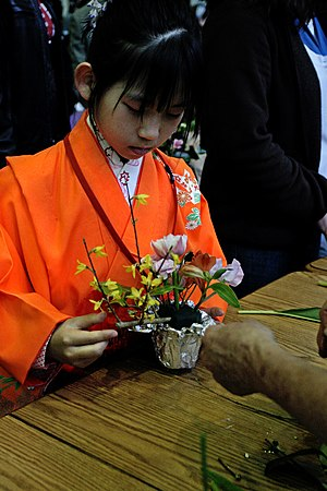 Floristry - Child learning the art of Ikebana. Today, florists in Japan also sell pre-arranged or done-while-you-wait ikebanas to go.