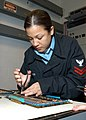 US Navy 050412-N-7279O-002 Aviation Electronics Technician 2nd Class Krisanna Moyer demonstrates how to repair a loose component in a circuit breaker.jpg