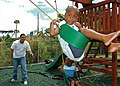 US Navy 060415-N-1161S-025 Aviation Machinist's Mate 2nd Class Augusto Baez assigned to Helicopter Anti-Submarine Squadron Seven (HS-7) plays with two local children on a swing set.jpg