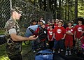 US Navy 080715-N-4649C-001 Master-At-Arms 3rd Class Ian Stephenson shows a group of children from the youth group Starbase Atlantis tools used to train military working dogs.jpg