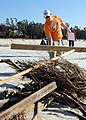 US Navy 081018-N-3857R-002 Construction Mechanic 2nd Class Karl Cox, assigned to Naval Mobile Construction Battalion (NMCB) 1, gathers storm debris off the beach in Gulfport, Miss.jpg