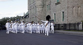 United States Navy Band - The Drum Major, Master Chief Joe D. Brown, wearing a bearskin hat and holding a ceremonial mace while leading members of the United States Navy Ceremonial Band as they march onto the parade grounds in front of the Quebec City Armoury as part of the opening ceremony of the Quebec Music Festival.