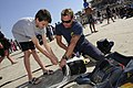 US Navy 100320-N-5366K-154 Chief Special Warfare Boat Operator J.C. Ledbetter shows a child how to pack his parachute after the team performed during the kick-off event for the 2010 Daytona Frogman Triathlon at Daytona Beach, F.jpg