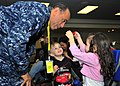 US Navy 110324-N-4044H-048 Navy chaplain Cmdr. Robert J. Thomas entertains children while their families wait for further instructions after passin.jpg