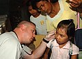 US Navy 110629-N-NJ145-150 Senior Chief Hospital Corpsman Tom Gilham treats a patient during a medical community service project during Cooperation.jpg