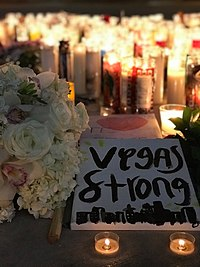 "In the background, there seems to be an endless number of candles glowing in the night. The foreground has a bouquet of white roses with a piece of paper that says ""Vegas Strong"". Under the text, there is a doodle of some city buildings."