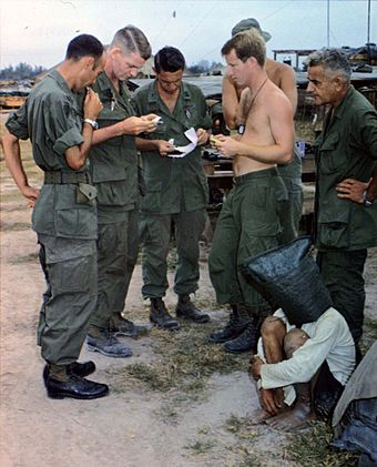 An alleged Viet Cong captured during an attack on an American outpost near the Cambodian border is interrogated. Vietconginterrogation.jpg