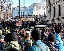 A large crowd of people stands in front of the Virginia State Capitol