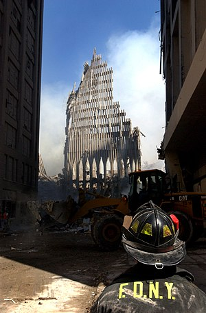Rescue and recovery effort after the September 11 attacks on the World Trade Center - A firefighter looks up at the remains of the South Tower. (September 13, 2001)