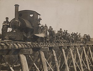 Walhalla railway line - A photograph showing workers on and beside train and sitting on pulleys, dressed in suits, ties and hats, posing on the bridge they have completed as part of the Walhalla Railway construction. A train engine is on wooden bridge in foreground.