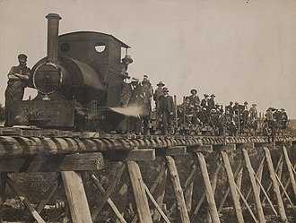 Walhalla railway line - A special train poses on a bridge of the Long Tunnel Extended timber tramway built to supply wood to the mines at Walhalla.  The photograph shows shareholders of the mine (?) dressed in suits, ties and hats sitting on log wagons, along with the Bagnall 0-4-0ST locomotive and its crew in the foreground.