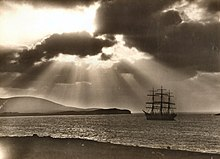A sepia-tone photograph of a 3-masted 19th century sailing vessel at sea with the shore in the foreground and dark hills beyond. The sun's rays cast light and shadows in the sky as they break through the clouds.