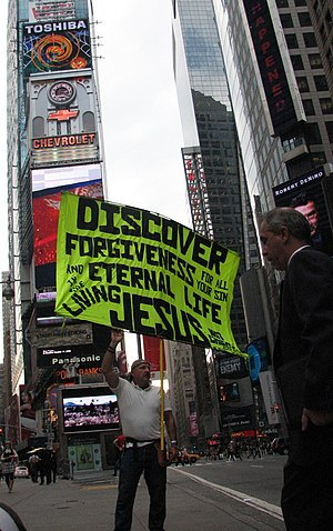 "Street Preacher holds sign that reads ""Di..."