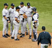 An in-game meeting on the mound featuring, from left to right, Derek Jeter, Robinson Cano, Alex Rodriguez, Jason Giambi, Randy Johnson, Jorge Posada, and Joe Torre