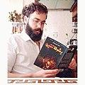 الكاتب عماد الدين زناف حاملا روايته بشر لا تنين.jpg