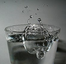 Short-term photography of a drinking glass filled with water.  The water surface is whirled up, a hole about 3 cm in diameter is in the water.  At the edge of the hole there is a crater rim that rises about 2 cm above the rest of the water surface.  Individual water droplets have detached from the crater rim and are about 4 cm above the edge of the glass.  Two thin arms of water run up from the crater rim, disintegrating into individual droplets.