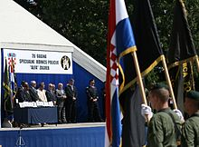 Troops bearing flags standing in front of a podium in a medal presentation ceremony