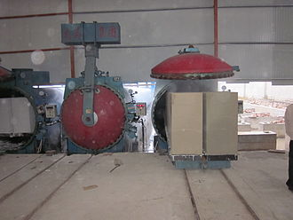 Autoclaved aerated concrete - On the right, green AAC blocks are being fed into an autoclave to be rapidly cured under heat and pressure