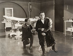 A Blind Bargain - In a medical operating room, Robert Sandell (Raymond McKee) is shocked by what he has read in the notepad that the Hunchback (Lon Chaney) has given him.