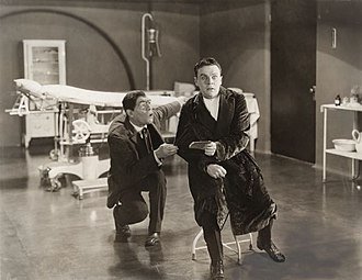 Raymond McKee - In an operating room, Robert Sandell (played by McKee) is shocked by what he has read in the notepad that the Hunchback (Lon Chaney) has given him in a scene from the silent horror film. A Blind Bargain (1922)