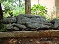 A stone sculpture of god Vishnu in reclining posture on display in Janapada Loka (Folk art museum).jpg