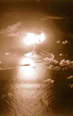 An atomic explosion lights up the night sky over a coral atoll