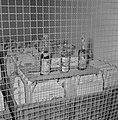 Achter een hekwerk staan kartonnen doosjes in houten kisten met erbovenop flesje, Bestanddeelnr 255-1918.jpg
