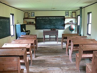 History of education in the United States - Well equipped one-room rural school (with desks, blackboard, books, globe, artwork, stove, piano) in Oklahoma early 20th century