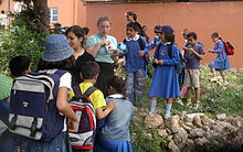 Several children dressed in blue wearing backpacks crowd around a small rock enclosure.