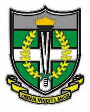 St. Augustine's College (Cape Coast) - The College Coat of Arms consists of a shield with a white cross on a green field. The lit torch is flanked by a laurel that is represented by yellow olive branches. The grey colour- a combination of white and black - signifies the combined efforts of the society of African Missionary (SAM) Fathers (whites) and African faithful in propagating the gospel.