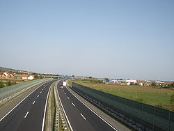 Six lane motorway running through rural area, separated by noise barriers.