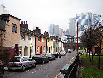 Blackwall, London - St Lawrence Cottages, a rare survivor of the old Blackwall. This shot (February 2006) faces west, and in the background is the old dock wall, beyond that the buildings around Canary Wharf.