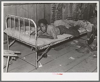 African American boy in a sharecropper shack, New Madrid County, 1938. Boy resting on bed in attic of sharecropper shack, New Madrid County, Missouri.jpg