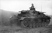 a black and white photograph of a tank driving along a dusty road