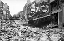 Three stationary tanks, one in the foreground and two in the rear, in a heavily damaged street; rubble covers the road.