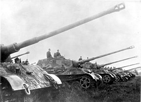 A row of seven large tanks lined up with their long guns pointing up at an angle, as if saluting.