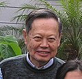 An old man, wearing a pullover is smiling.