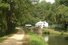 Photograph of a dirt towpath beside a canal with a lock with a house in the background