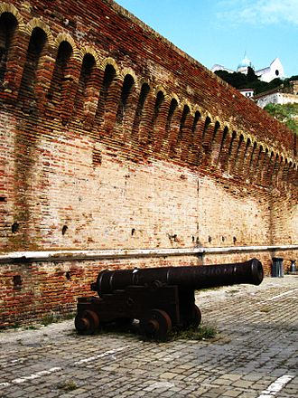 Ancona - A cannon situated near the Arch of Trajan, with the Cattedrale San Ciriaco visible in the background.