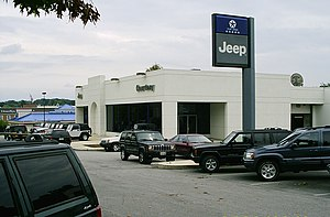 Car dealership - Typical car dealership (in this case a Jeep dealer) selling used cars outside, new cars in the showroom, as well as a vehicle entrance to the parts and service area in the back of the building.