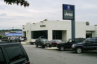 Car dealership - Typical car dealership (in this case a Jeep dealer) selling used cars outside, new cars in the showroom, as well as a vehicle entrance to the parts and service area in the back of the building