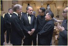 Trois hommes debout dans un salon discutent au milieu d'une assemblée d'hommes en costume de soirée