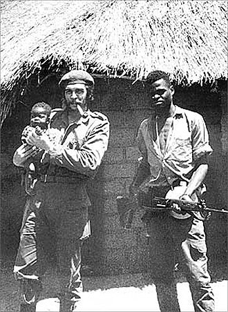 Ñancahuazú Guerrilla - Che Guevara at his basecamp holding a local African infant and standing next to a fellow Afro-Cuban soldier in the Congo during the Congo Crisis, 1965.